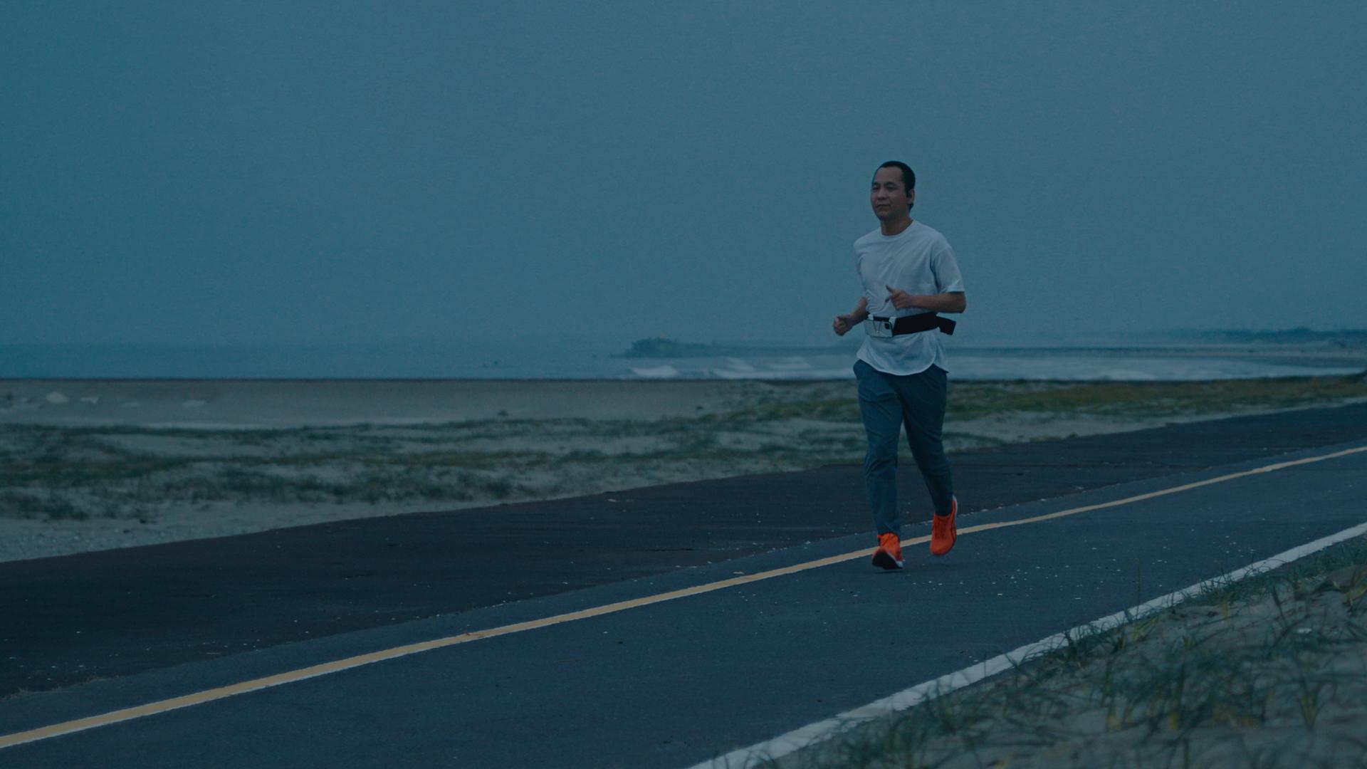 写真:朝日が上る時間帯に、浜辺が見える海沿いのコースを一人で走る御園さん。