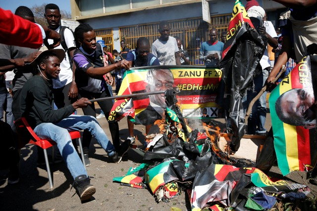 Supporters of the opposition Movement for Democratic Change party (MDC) of Nelson Chamisa burn an election banner with the face of Zimbabwe's President Emmerson Mnangagwa in Harare, Zimbabwe, August 1, 2018.