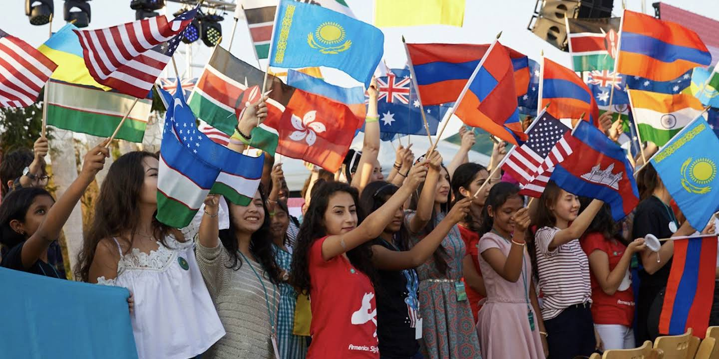 A group of female students from different international backgrounds waving flags from different countries.