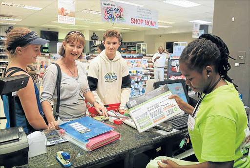 PREPARING FOR SCHOOL: Meredith Judd with her son, Matthew Judd, and daughter Ashleigh Judd buy stationery at Waltons stationers in Vincent yesterday Picture: SINO MAJANGAZA
