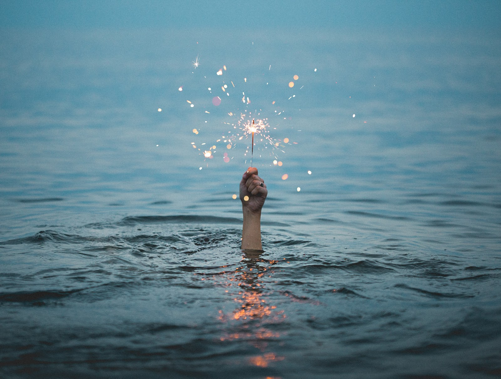 photo of a hand rising out of a lake with a lit sparkler