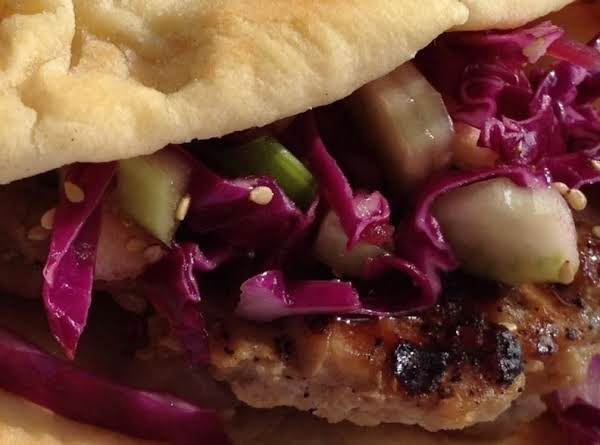 This Piggy Bun  Features A Marinated And Tenderized Boneless Pork Cutlet,  Served On Puffy Naan Bun And Topped With Sesame Slaw.