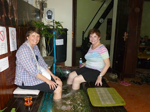 "Photo: When we had some free time, Kathie and I indulged in a ""fish foot massage"".  Small tiger fish eat the dead skin off your feet.  It tickled."