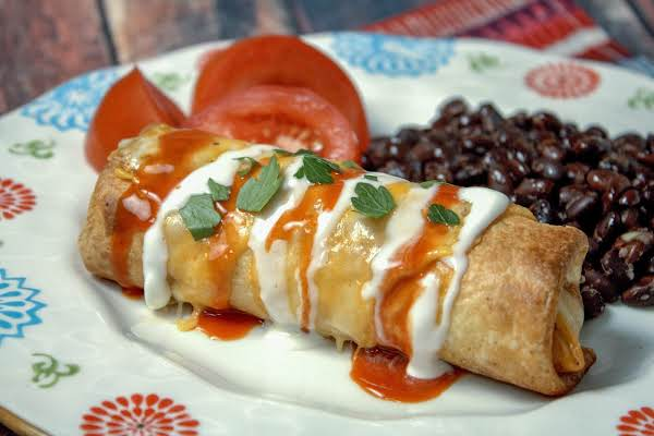 Baked Chimichanga On A Plate Drizzled With Sour Cream And Taco Sauce.