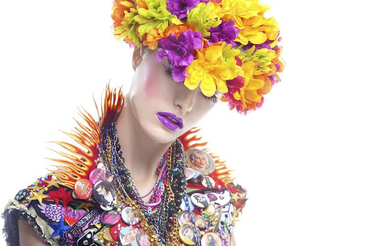 vrouw met fleurige bloemenhoed in kleurige jurk met korte mouwen