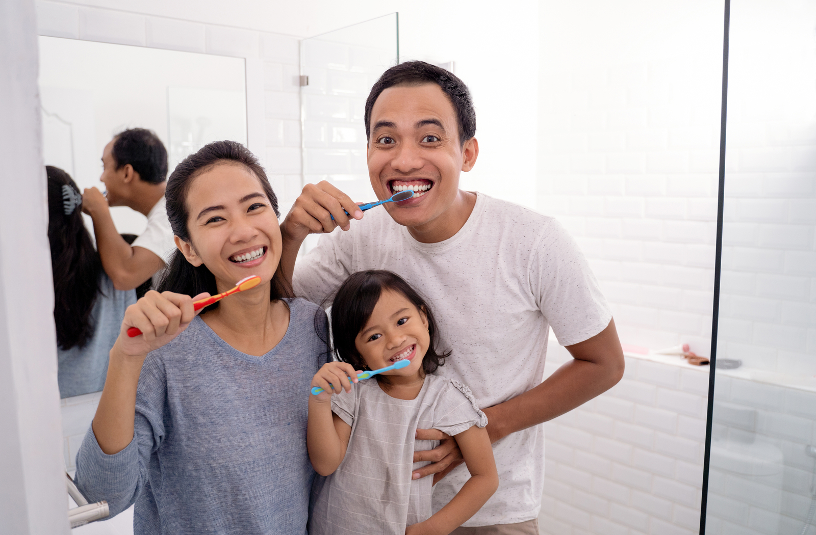 Child mimicking her parents as they brush their teeth as a family.