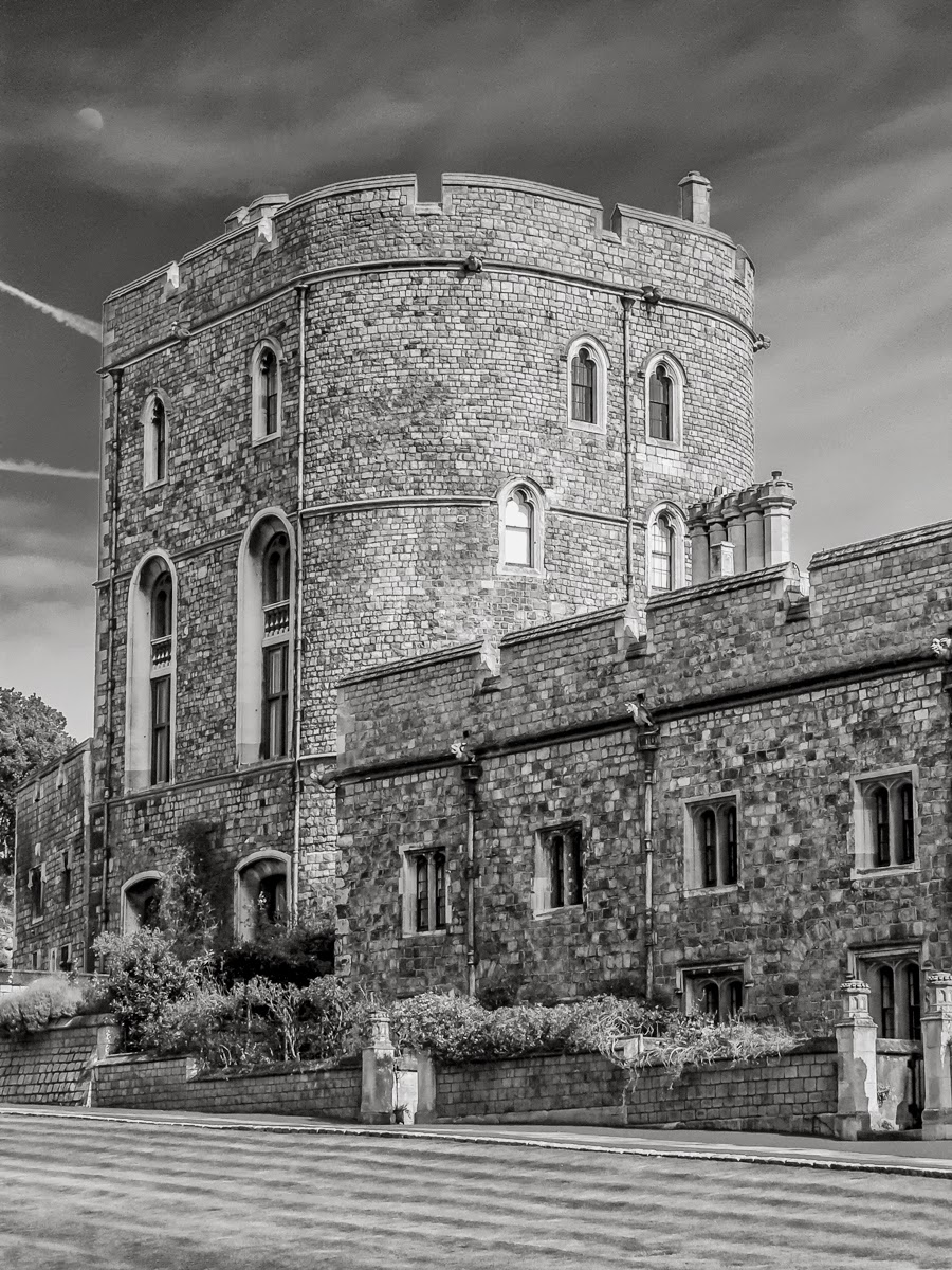 """Photo: A Queen's Castle Is Her Home I bet it's hard to heat the place up in the winter!  Windsor Castle - April 2006. The Royal Family does not actually reside in this part of the castle. That's up the slope somewhat.  The tone processing consisted of basic adjustments in Lightroom 4 followed by application of custom b/w settings in DxO FilmPack 3, which included a deep orange filter to darken the sky to bring out the moon and castle tower itself, as well as a """"large format"""" grain setting. I also did a bit of cloning and content-aware fill to get rid of some antennas, cables and other distractions.  #Travel  #England  #WindsorCastle  #Castles  #BlackAndWhitePhotography  #BlackAndWhite  #DxO"""