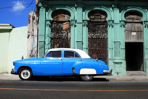 Cuba-Blue-Car-Profile-in-Front-of-Teal-Building_01.jpg - Vintage cars dot the streets of Havana.