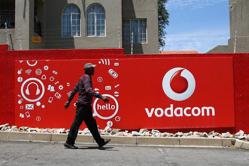 A pedestrian walks past a Vodacom-branded billboard at a taxi rank near Vodaworld, the headquarters of Vodacom Group Ltd. File photo