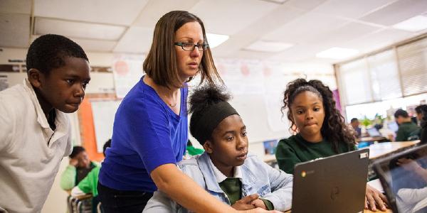 A teacher helping students on a chromebook