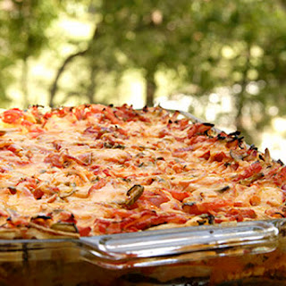 Ground Beef, Refried Beans And Tomatoes Are Combined With Chiles And Taco Sauce, Then Layered In A Casserole With Tortillas And Cheese, And Baked..