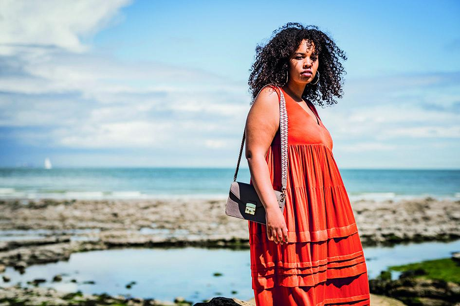 Black woman standing on the beach wearing sleeveless red dress with gathered tiers and horizontal pleats on skirt.
