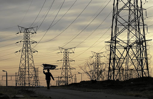 Yields: A woman carries firewood under Eskom's electricity pylons in Soweto. Yields on the power utility's bonds remain little changed and broadly in line with what they were at the beginning of 2017. Picture: REUTERS