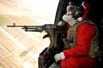 Photo: Santa takes reasonable precautions while delivering presents in Helmand Province. Door Gunner Petty Officer Richard Symonds (Royal Navy) dresses as Santa as he delivers mail and presents to troops around Helmand province.Servicemen and women serving in Afghanistan have been enjoying the festivities of Christmas Day, with a traditional dinner and lots of seasonal fun.The MOD has sent over six tonnes of festive food to Afghanistan to give our forces a taste of Christmas while on operations, including:Two tonnes of turkey; One and a half tonnes of gammon; One and a half tonnes of sprouts;200 Kilos of cranberry sauce;1000 iced Christmas cakes; A tonne of Christmas pudding; 15,000 mince pies; and 45,000 After Eight mints.Charity ÔUK4UThanks!Õ became SantaÕs little helper as they provided 22,500 Christmas boxes to troops all over the world - containing a host of goodies bought with money donated from members of the public. The presents were unwrapped by troops serving in Afghanistan on Christmas Day.While work continued for many of the troops, most had the chance to let their hair down a little with fun and games, sports competitions, and quizzes. Church services were also held by the team of Padres to ensure the true spirit of Christmas was not forgotten. And everyone received an extra 30 minutes free time on their welfare phone card to ensure they could wish their family and friends a merry Christmas.