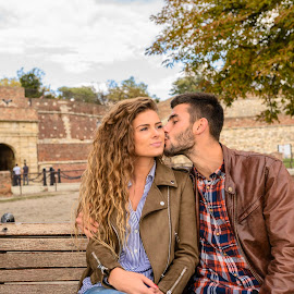Young man showing the love by Vera Arsic - People Couples ( young women, romance, two people, friendship, heterosexual couple, city life, togetherness, young adult, kissing, model, attractive, tree, lovers, lifestyles, girlfriend, enjoyment, color image, love - emotion, adult, weekend activities, photography, handsome, couple - relationship, city, 20-29 years, boyfriend, casual clothing, affectionate, modern, romantic, happiness, joy, dating, flirting, caucasian ethnicity, wooden bench, public park, nature, carefree, sexy, intimate, young men, people, young couple, outdoors, bonding, growth, feelings, fun, fashion )