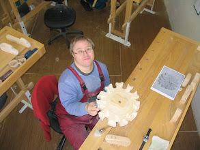 Photo: Pracovník zhotovuje hodiny ve tvaru sluníčka