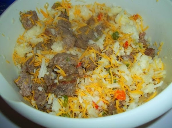 In a medium sized bowl; mix sausage mixture, 1 1/2 cup cheddar and hash...