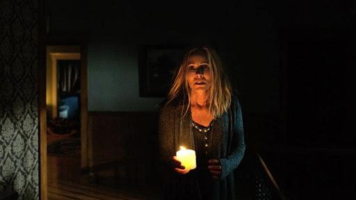 Mujer camina en una habitacion oscura con una vela enla mano