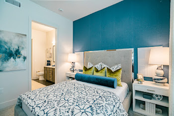 B1 model bedroom with neutral carpet and blue accent wall