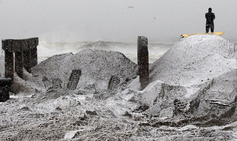Photo: NEW YORK, NY - NOVEMBER 07: Surfer ''Mandog'' stands on a pile of sand collected from the streets and placed back on the beach amid the destroyed boardwalk as he watches a friend surf while a Nor'Easter approaches in the Rockaway neighborhood on November 7, 2012 in the Queens borough of New York City. The sand is placed back on the beach to clear the streets and also to help prevent possible storm surge. The Rockaway Peninsula was especially hard hit by Superstorm Sandy and some are evacuating ahead to the coming storm. (Photo by Mario Tama/Getty Images)