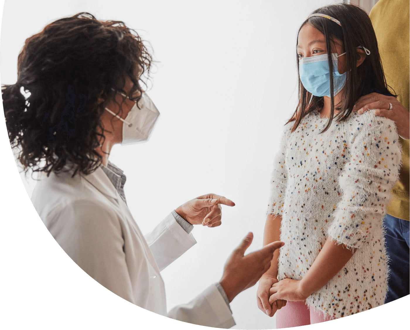 Doctor in mask talking to child