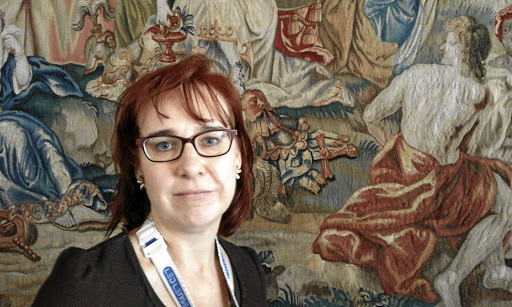 Intricate detail: Textile conservator Louise Man-Nel in front of the tapestry, Victory, one of a set of four in the house. Picture: JANINE STEPHEN