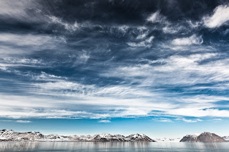 Photo: Polarised Sky Svalbard, Norwegian Arctic From the blog http://www.kylefoto.com  This sky was particularly beautiful. Sometimes it's not about the extraordinary landscapes that are under my feet, but the canvas of ever changing colour and texture above in the sky.  Photographic Details: Shot at the brightest exposure I could allow myself in order to capture the most detail, I also used a circular polarizer. A handy little filter known for darkening the blue sky in order to get the sky to pop. If the sun is in the right direction often the piece of sky 90 degrees perpendicular to it is greatly effected by the polarizer, adding a bit more drama to the image.  The best way to visualise which part of the sky will be greatly effected by a polariser is by making a 90 degree angle with your thumb and index finger, like making a pretend gun with your hand. If you keep your thumb pointed directly at the sun at all times, any direction you can then point your index finger will tell you where the sky is mostly effected by the polariser, voila! Your hand is a polarised sky finder!  1/125s f/9.0 ISO100 16mm