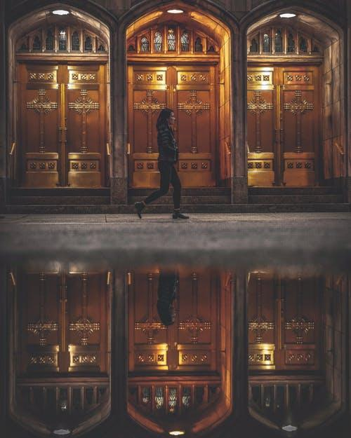 Woman Walking Near Closed Doors of Building Near Water With Self Reflection