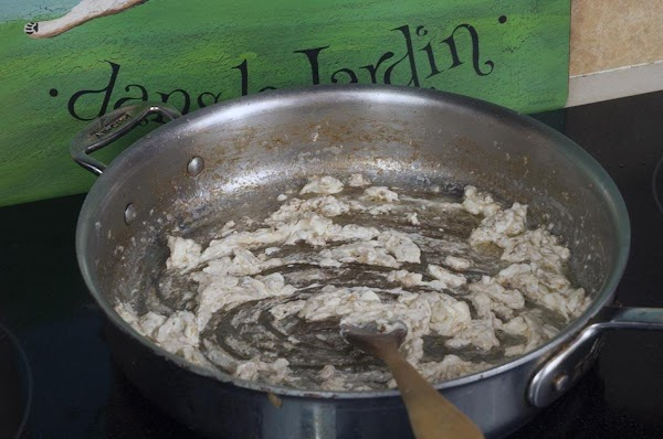 Add the cream cheese to the pan, and begin to whisk into the garlic.