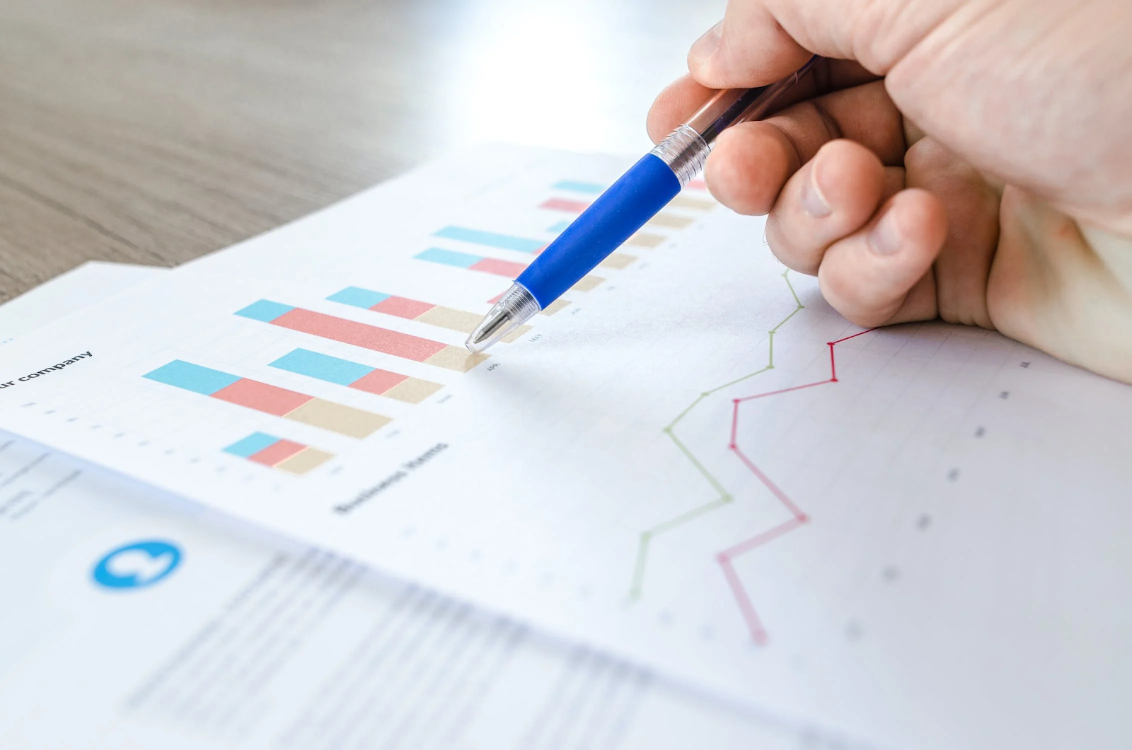 Person holding blue pen pointing at graphs