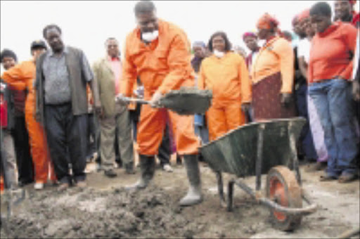 GETTING STUCK IN: Minister of Land and Rural Development Gugile Nkwinti scoops concrete from a wheelbarrow as he helps to build toilets at a school in Muyexe village at the weekend.Pic: CHESTER MAKANA. 19/07/2009. © Sowetan.