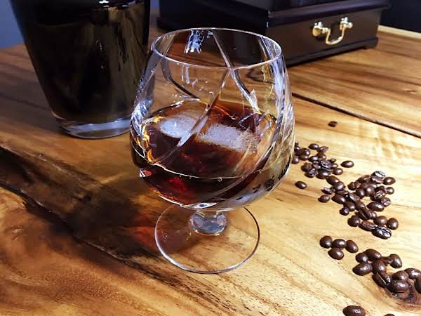 A Cocktail On Ice In A Snifter Glass With Coffee Beans Surrounding It.