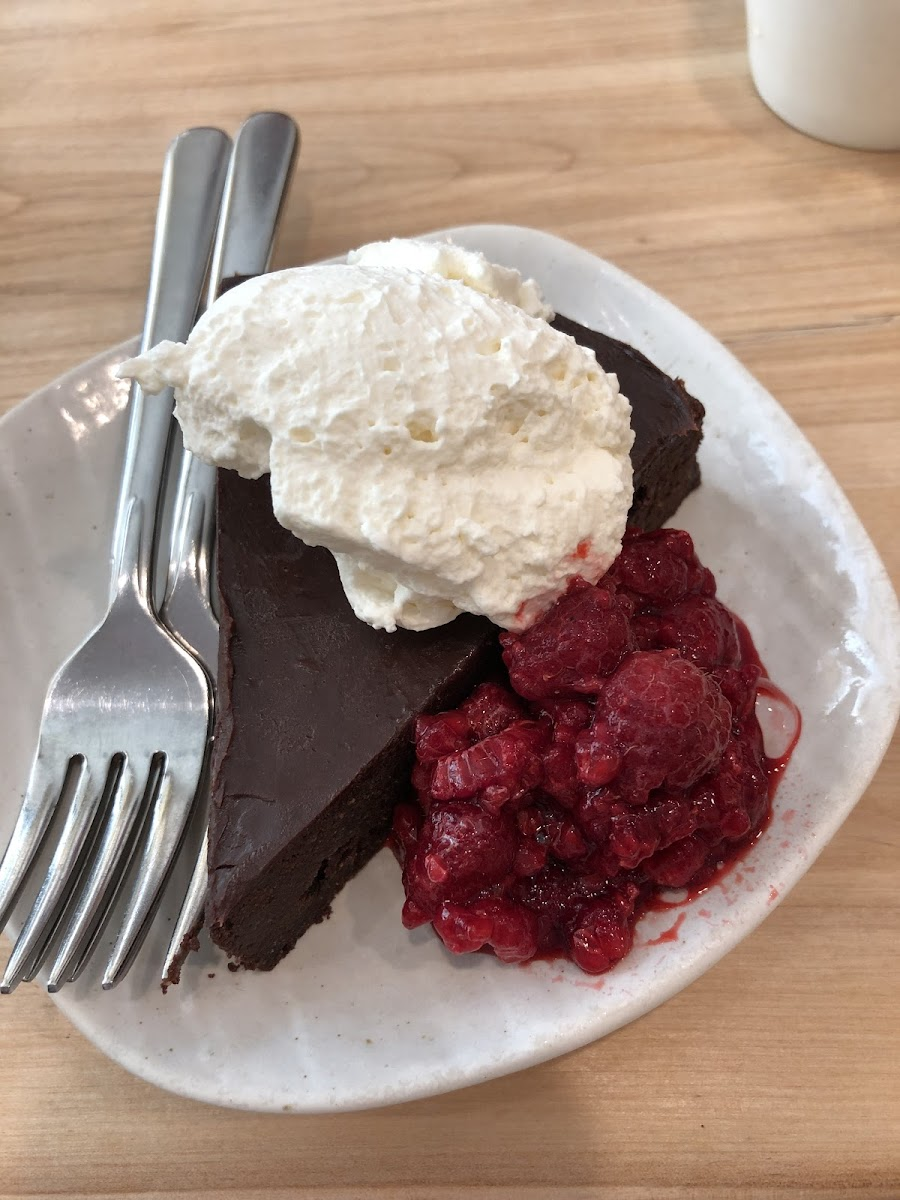 Flourless Chocolate Cake with whipped cream and raspberries. Yum!