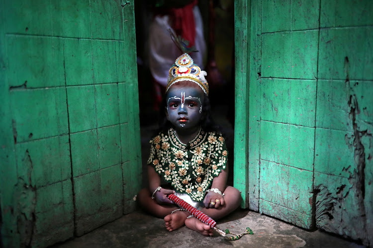 A child sits on a doorstep, dressed as Lord Krishna, during Janmashtami festival, which marks the birth anniversary of Lord Krishna in Dhaka, Bangladesh.