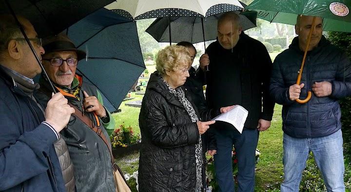 Walborg Schröder redet vor Gedenkenden mit Regenschirmen auf dem Friedhof.