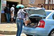 A customer returns  products at an Enterprise outlet after a recall by Health Minister Aaron Motsoaledi following a listeria outbreak on March 5.