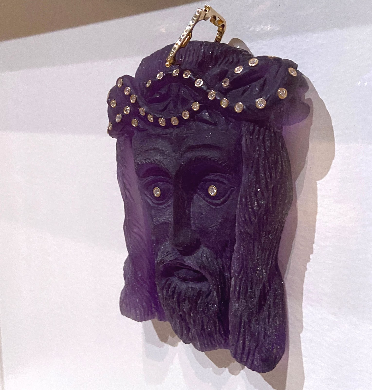 Image: A Jesus piece behind glass is hung on the wall of the gallery. The carving features the face of Jesus Christ with a loop at the top; the entire sculpture is painted purple. The eyes have been embellished with gems that resemble small diamonds set in gold. These embellishments also make up the crown on Jesus' head. Photo by Jessica Hammie.