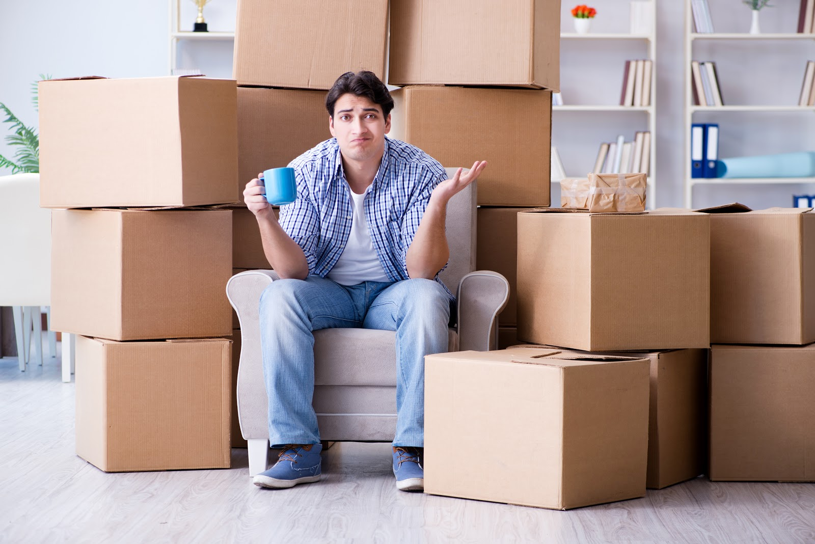 A man looking puzzled and stressed sitting among moving boxes