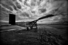 klein oud vliegtuig op een landingsbaan tegen een sombere lucht