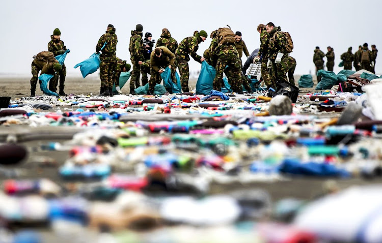 Netherlands' army soldiers take part in the cleaning of the coastline of Schiermonnikoog on January 4 2019 in the Dutch Frisian Island, two days after some 270 containers tumbled from the Panama-registered MSC Zoe, one of the world's biggest cargo ships in rough weather. Picture: AFP/REMKO DE WAAL
