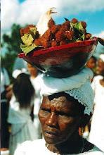Photo: Dona Maria, representando uma mucama, leva na cabeça uma tigela de madeira com milho, urucum e algumas ervas, revivendo o tempo em que as escravas negras comandavam as cozinhas de seus senhores.
