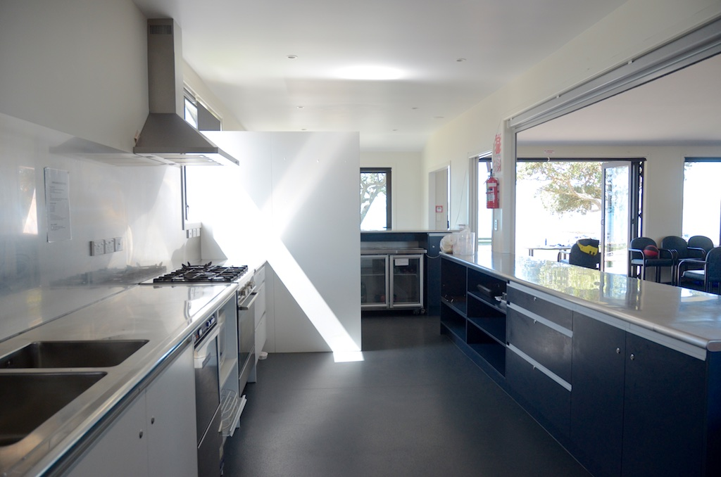 Photo: Wakatere kitchen: stainless steel benchtops, commercial fridges with glass fronts, large open shelving, commercial dishwasher and large oven, roller screen to divide kitchen from hall.