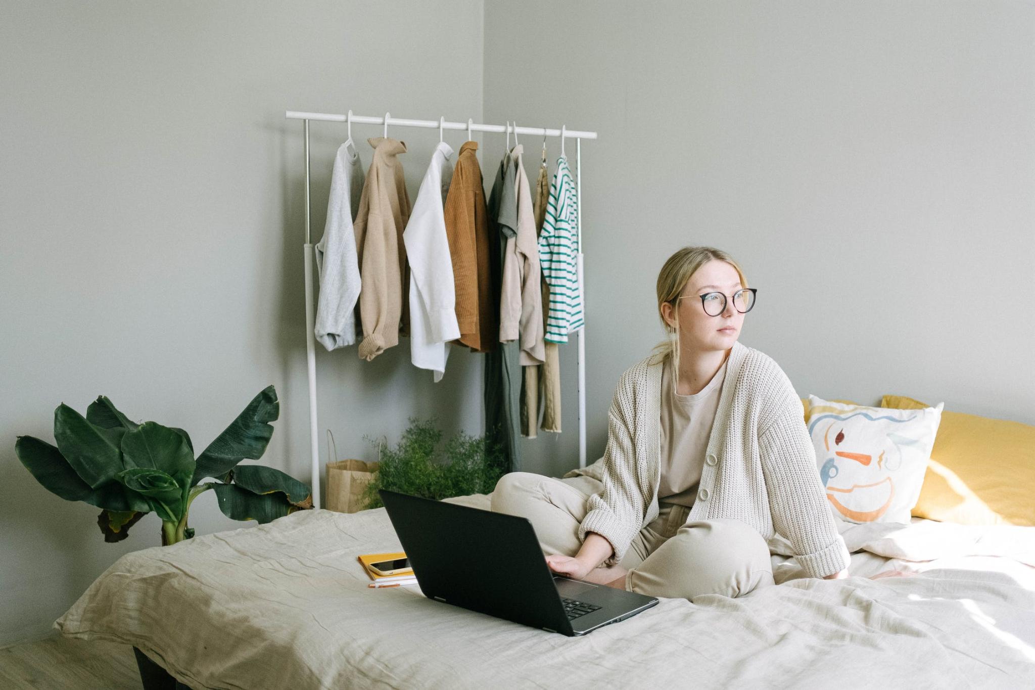 žena sedí na posteli s laptopom a hľadí von oknom