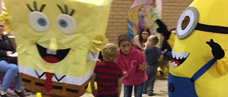 two people in a spongebob and a minion suit at a kids party