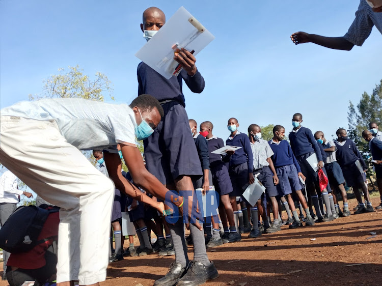 A teacher frisks KCPE candidates at Joel Omino Primary School in Kisumu before the start the 2020 KCPE exams on March 22, 2021/DANIEL OGENDO