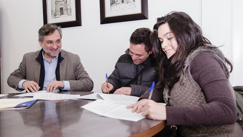 El diputado provincial firma un contrato con nuevos compradores de vivienda. L
