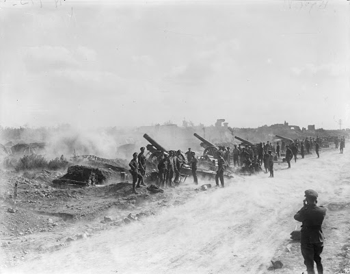 Battery of 8-inch howitzers (Royal Garrison Artillery) in action on the roadside at St. Leger. Note dust rising from road as result of concussion of discharge, 29 August 1918.
