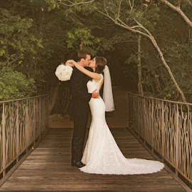 Kissing At the Old Bridge by Matthew Chambers - Wedding Bride & Groom ( bride, love, dress, groom, tuxedo, bouquet, wood, bridge, kiss )