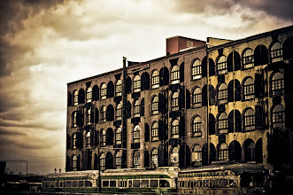"""Photo: """"Times tells its own tales...""""  480 Brunt Street is a Civil War-era storehouse located in the Red Hook Waterfront Historic District in Brooklyn.  Red Hook, located in Northwestern Brooklyn was settled in 1636 by Dutch Colonists who named the area Roode Hoek (red point) after the red hue of the soil and because the area jutted out into the water. Due to its waterfront location, ships from all over the world would dock at Red Hook to exchange cargo and make repairs for well over a century. When many of the shipyards were relocated in the 20th century, the area fell was marked by significant urban decay.  The building in this photo, known as the Red Hook Stores, was built in 1869 by the builder William Beard. Beard, who was an Irish immigrant made millions via his building and railroad empire. At the end of the Civil War, New York City was receiving such a large amount of goods that Manhattan could not handle all of the cargo. Brooklyn's waterfront became the alternative and warehouses like this one played a crucial role in offloading cargo like grain, cotton, hemp, jute, indigo, leather, fruits, tobacco, vegetables, cocoa beans and coffee. This building now houses a Fairway Market and apartment residences. The beautiful iron shutters that give this warehouse building so much charm were initially built to protect the precious cargo stored in the warehouse from the elements.  The decayed trolley cars which sit in the foreground also have an interesting link to the past. In the 20th century there were many trolley lines that criss-crossed the Brooklyn landscape serving as transportation for residents. The trolleys were in use until the 1950s. To celebrate the trolleys that would have been seen here for many years, these trolleys were acquired and put in front of the Red Hook Stores permanently. They aren't from New York City originally though. The trolley cars were acquired from Boston and Oslo and were repainted to match the original color scheme of the trolleys """