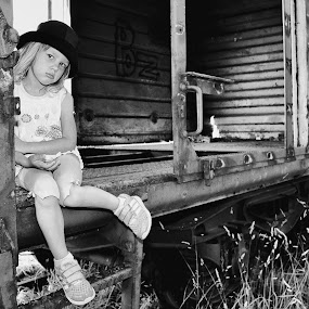 A Girl in a hat by Mario Toth - Black & White Portraits & People ( ladder, wooden, girl, wheel, sadness, grass, black and white, sad, wagon, train, abandoned, hat,  )